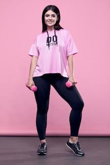 Портрет шикарной фигуры позитивной латинской женщины в розовой спортивной толстовке с гантелями на розовом