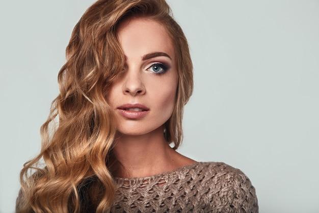 Портрет красивой улыбающейся белокурой женщины с длинными волосами