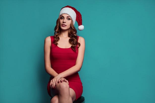 Элегантная красивая женщина в красном платье и новогодней шапке