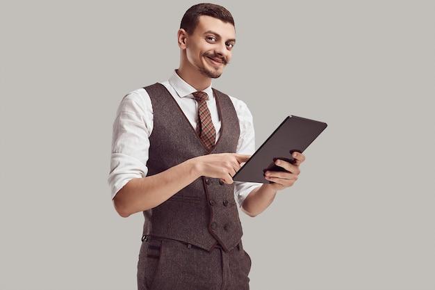 茶色のスーツでハンサムな若いアラビア語ビジネスマンがタブレットを保持します