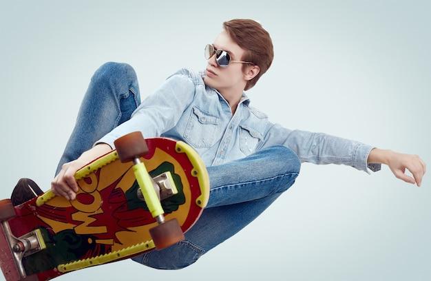 Красивый хипстерский человек в джинсовой куртке делает сальто на стильном скейтборде