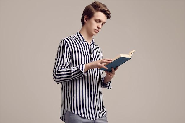 Молодой красавец в полосатой рубашке читает книгу на сером