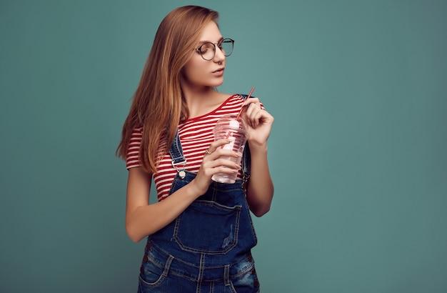 デニムのオーバーオールとソーダ水とメガネでかわいい十代の少女