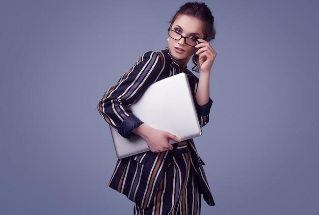ファッションスーツとノートとメガネでエレガントなグラマー女性