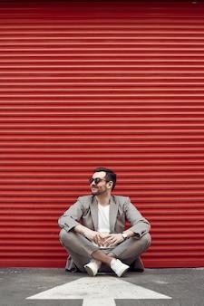 赤いゲートの近くのファッションスーツの若いハンサムな残忍な男