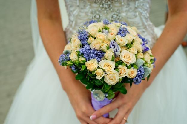 Молодая невеста держит нежный букет роз