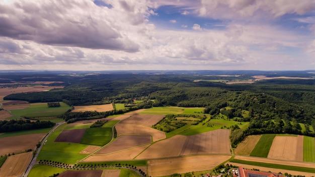 農業分野と白い雲と青い空の美しい空撮。