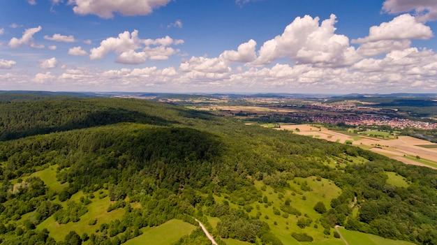 緑の森と白い雲と青い空の丘の美しい景色。空撮。