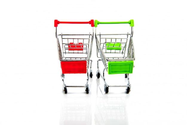 白で隔離される空の赤と緑のショッピングカート