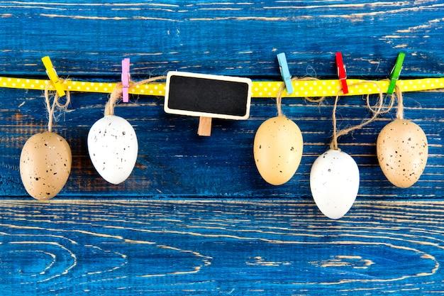 Пасхальные яйца на веревке на деревянной синей