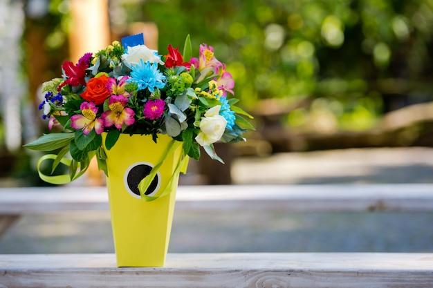 Красивый подарок букет в желтой вазе на деревянной скамейке. свадебный декор.