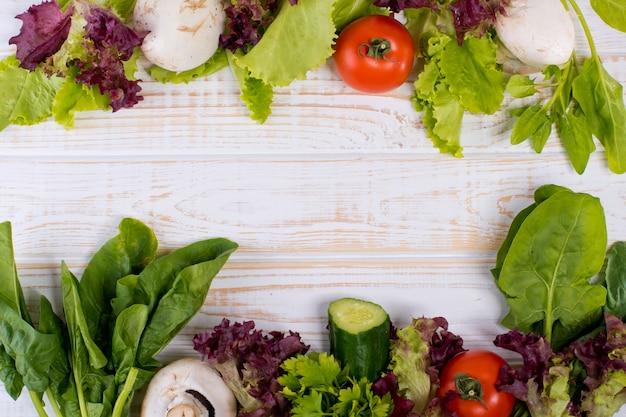 Рамка из свежих овощей, салата, помидоров, огурцов, грибов, петрушки, шпината на белом деревянном