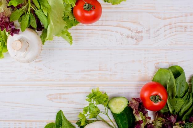 Рамка из свежих овощей, салат, помидоры, огурцы, грибы, петрушка, шпинат на белом фоне деревянные. кухонный фон.