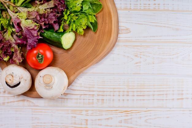 Рамка из свежих овощей, салата, помидоров, огурцов, грибов, петрушки, шпината на деревянном
