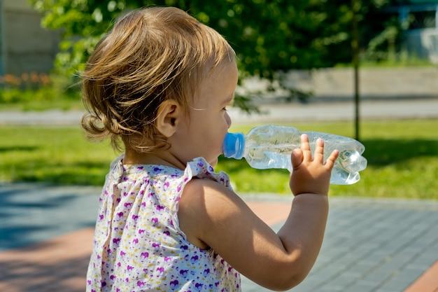 Маленькая девочка пьет воду из бутылки. вид сбоку. крупный план.