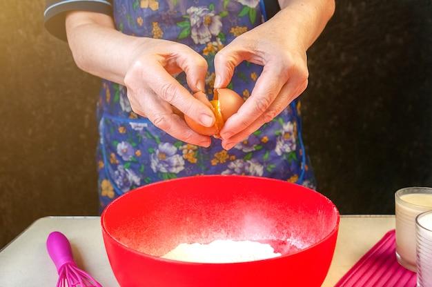 Выпечка ингредиенты и посуда для приготовления бисквита. процесс приготовления бисквита. женщина разбивает яйцо в тесте.