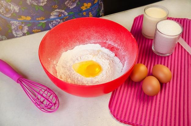 Выпечка ингредиенты и посуда для приготовления бисквита. чаша из муки, яйца, сахар, сгущенное молоко, венчик, силиконовый шпатель.