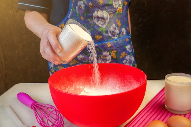 Выпечка ингредиенты и посуда для приготовления бисквита. процесс приготовления бисквита. женщина добавляет сахар в тесто.