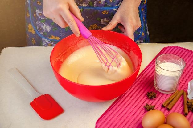 Выпечка ингредиенты и посуда для приготовления бисквита. процесс приготовления бисквита. женщина, смешивая тесто