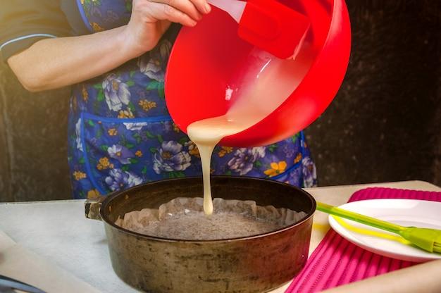 Выпечка ингредиенты и посуда для приготовления бисквита. процесс приготовления бисквита. женщина выливает тесто в форму для выпечки