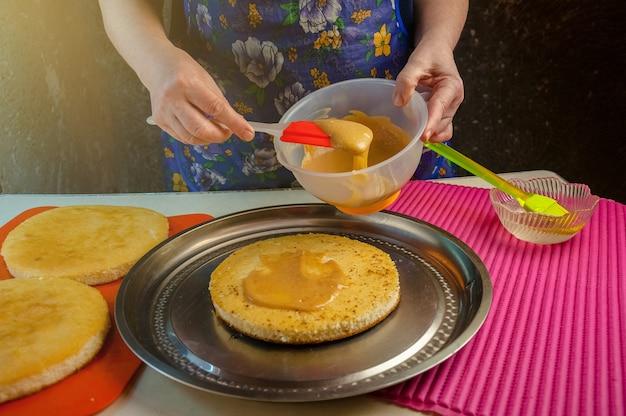 Выпечка ингредиенты и посуда для приготовления бисквита. процесс приготовления бисквита. женщина кладет крем на торты