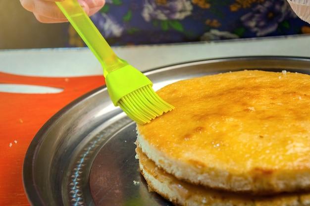 Выпечка ингредиенты и посуда для приготовления бисквита. процесс приготовления бисквита. женщина пропитывает пирожные с сиропом