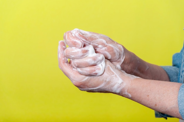 パンデミック時に石鹸で手を丁寧に洗うクローズアップ女性。