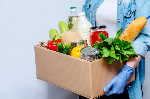 Женщина в перчатках держит ящик для пожертвований продовольственные товары для людей в изоляции. основные товары: масло, консервы, злаки, молоко, овощи, фрукты