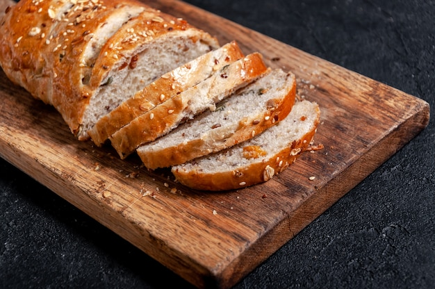 Домашний нарезанный хлеб из цельнозерновой муки с зернами льна и кунжутом на деревянной доске на темном столе