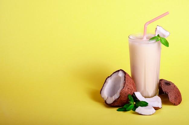 ピニャコラーダ-パイナップルジュース、ココナッツミルク、ラム酒とトロピカルカクテル。ひびの入ったココナッツと黄色の背景にミントの新鮮な夏の飲み物。あなたのテキストのコピースペース。