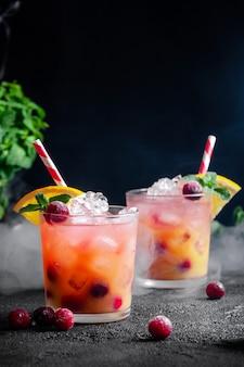Коктейль с ромом или содовой, клюквой, апельсиновым соком, лаймом и мятой в бокале с дымом на темно-серой стене