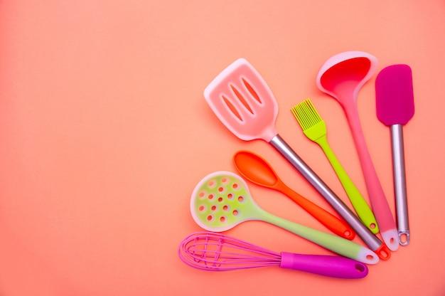 Различные цветные силиконовые кухонные принадлежности на фоне кораллов. скопируйте место для вашего текста
