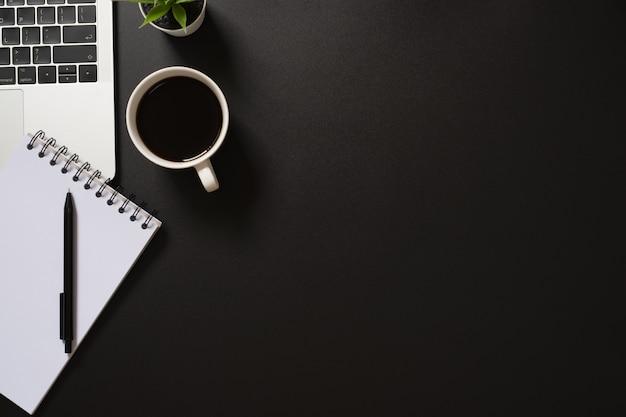 コンピューター、メモ帳、ペン、コーヒー、黒の背景に植物とデスクオフィストップビュー。