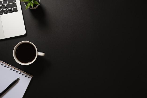 コンピューター、ペン、コーヒー、黒の植物とデスクオフィストップビュー