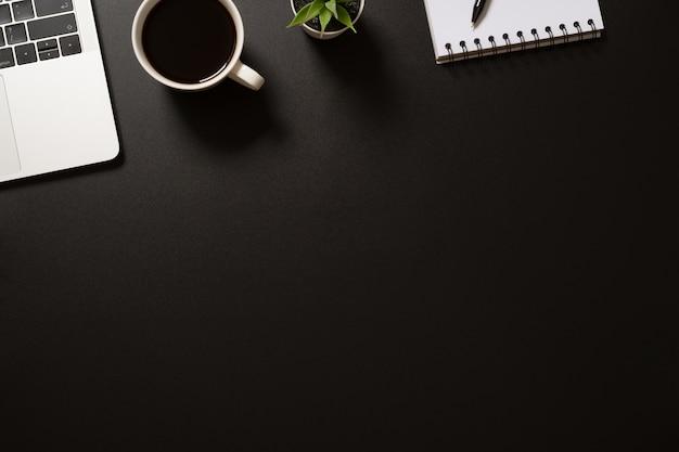 コンピューター、メモ帳、ペン、コーヒー、黒の植物とデスクオフィストップビュー