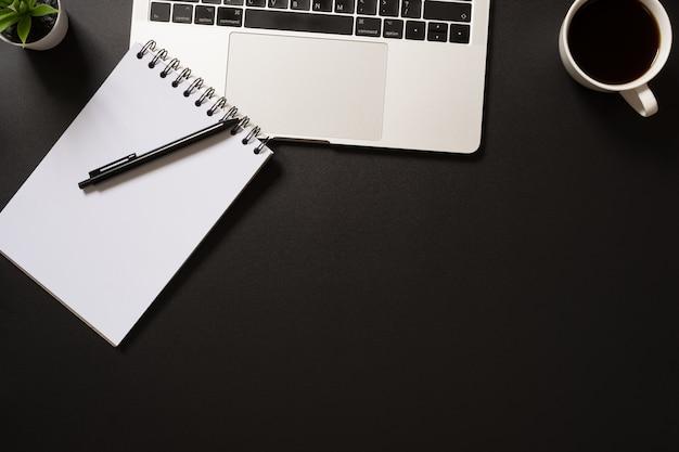 コンピューター、空白のメモ帳、ペン、コーヒー、黒の植物とデスクオフィストップビュー