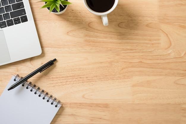フレイレイアウト、ラップトップコンピューター、キーボード、メモ帳、コーヒー、ペン、緑の植物のトップビューオフィステーブルデスク
