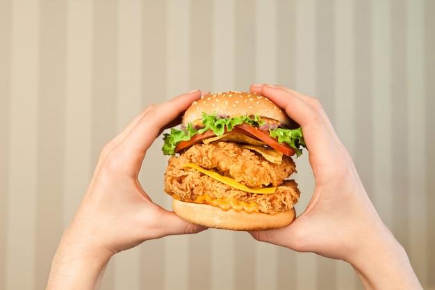 Бургер в женских руках на светлом фоне