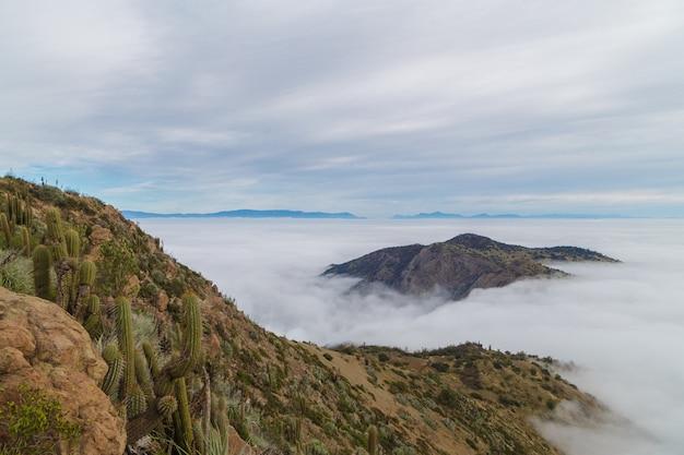 Вид на вершину горы, окруженные облаками