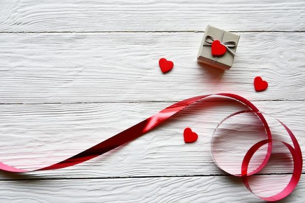 赤いリボン、小さな木製の赤いハート、白い机の上のギフトボックス。バレンタインデーのコンセプト