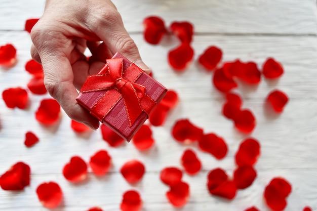 ギフト用の箱と赤いバラの花びらを持つ男性の手。バレンタインデーのコンセプト