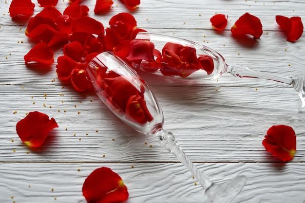 赤いバラの花びらがワイングラスからこぼれた。バレンタインデーのコンセプト