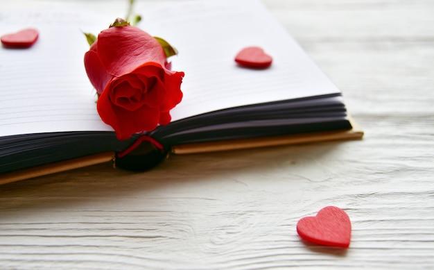 Красная роза на книжном развороте и маленькие деревянные красные сердечки