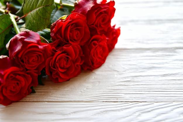 赤いバラの花束と白い木製。バレンタインデーのコンセプト