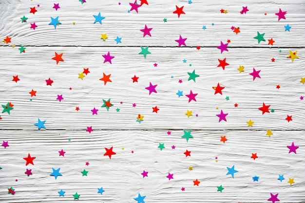 Звездообразный конфетти на белом фоне деревянные. праздничный фон. может использоваться в качестве фона для открытки на день рождения, рождество или новый год.