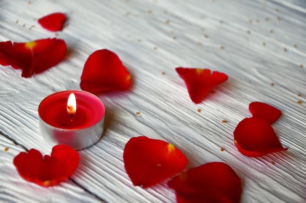 赤いバラの花びらと白い木製の赤いろうそく。バレンタインデーのコンセプト