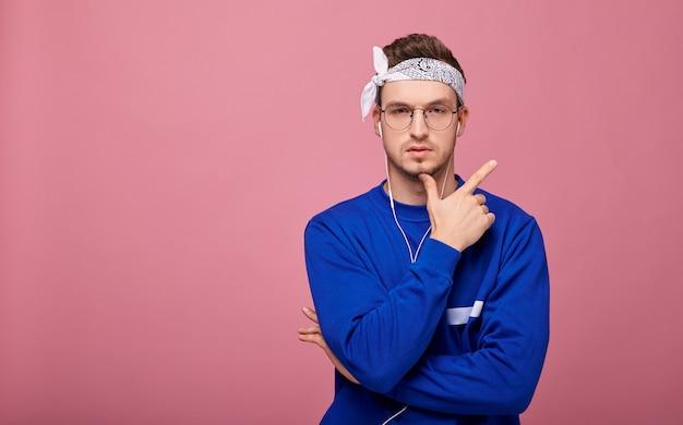 Спокойный мальчик в очках в синем свитере для прослушивания музыки