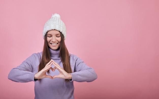 Веселая девушка в зимней одежде или весеннее шоу пальчикового сердца