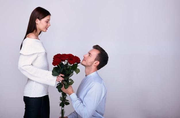 Молодой любовник стоит на одном колене и дарит своей подруге красные розы.