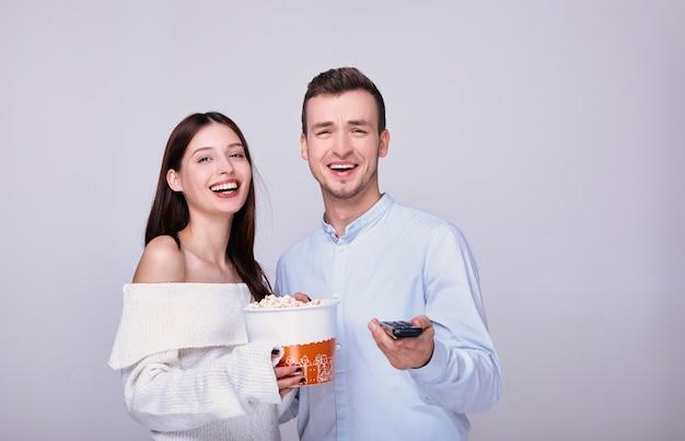 Милая пара в уютной обстановке дома смотрит душевный веселый фильм в домашнем кинотеатре